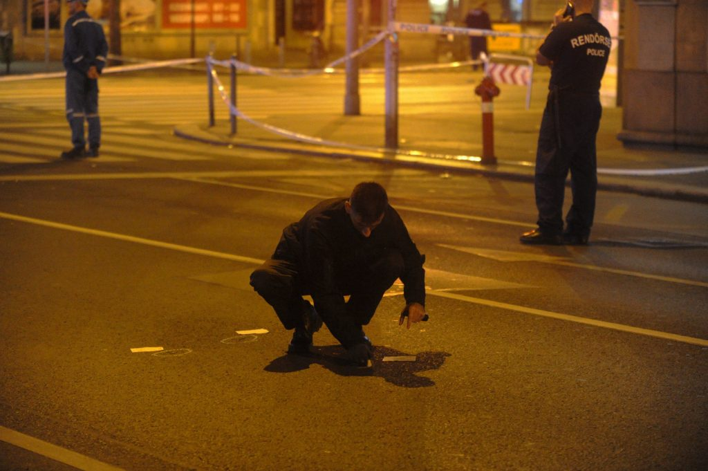 A police officer examines the area of the scene in central Budapest, Hungary, early Sunday, Sept. 25,  after an explosion of yet unknown origin occurred in a shop late Saturday night injuring two patrolling policemen. (Zoltan Mihadak/MTI via AP)