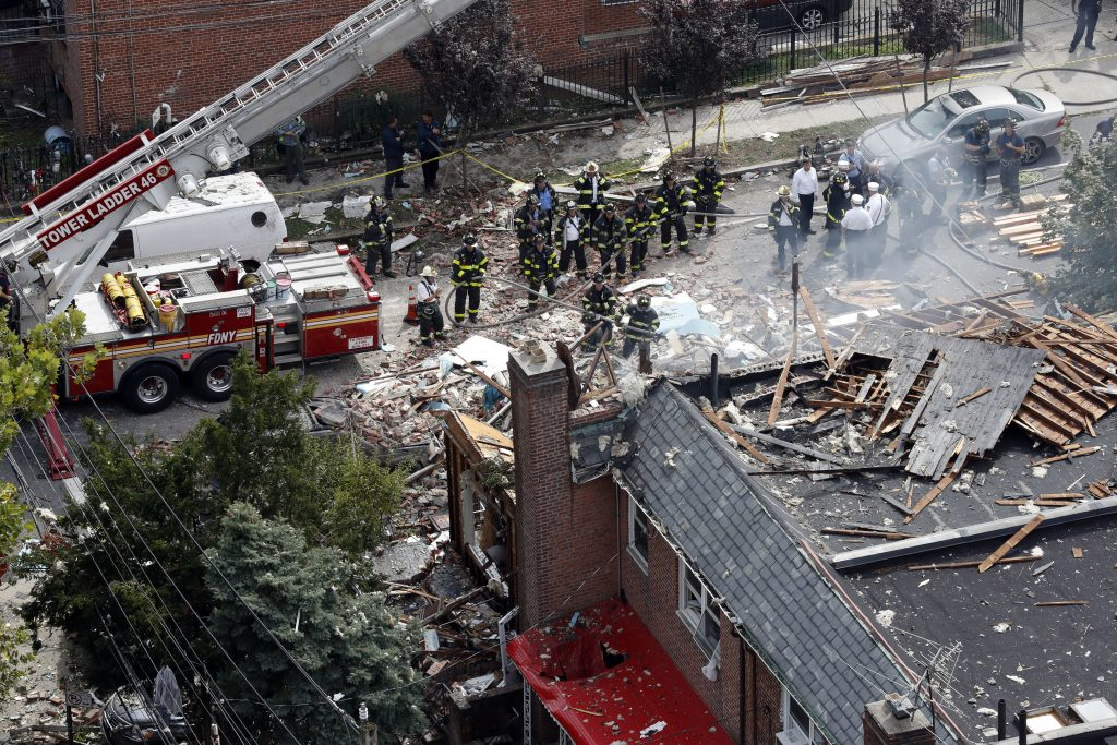 Emergency service personnel work at the scene of the explosion in the Bronx on Tuesday. (AP Photo/Mary Altaffer)