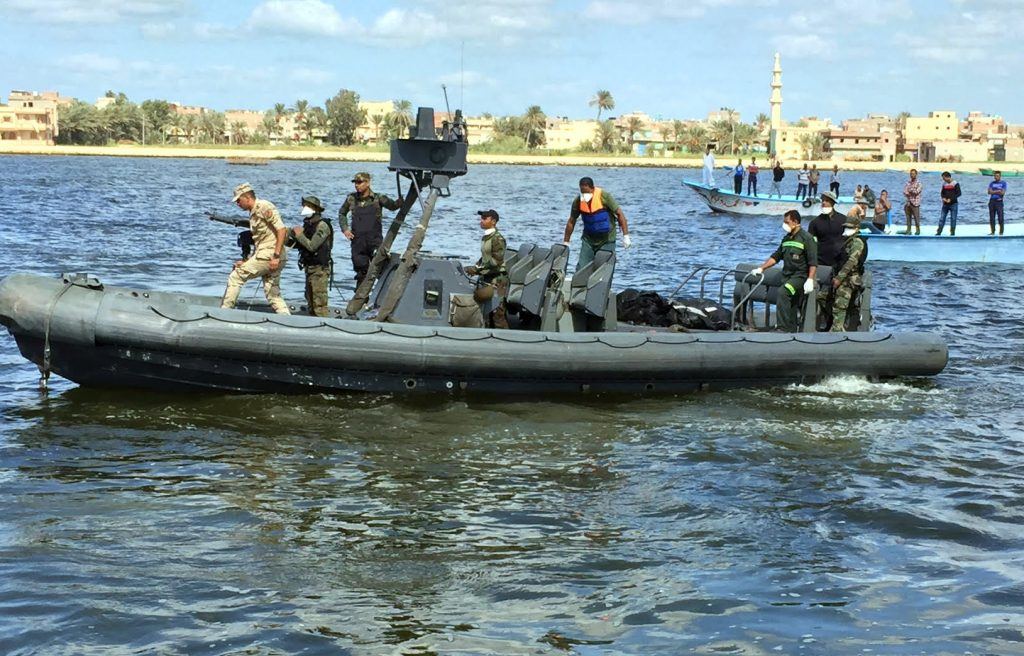 Egyptian Coast Guard and rescue workers bring ashore bodies recovered from the capsized boat, in Rosetta, Egypt, on Tuesday. (AP Photo/Maggie Michael)