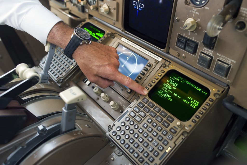 UPS Capt. Christian Kast points to the Data Communications Data Comm technology in the cockpit of an UPS Boeing 767-300F aircraft at Dulles International Airport Air Traffic Control Tower in Sterling, Va. (AP Photo/Cliff Owen)