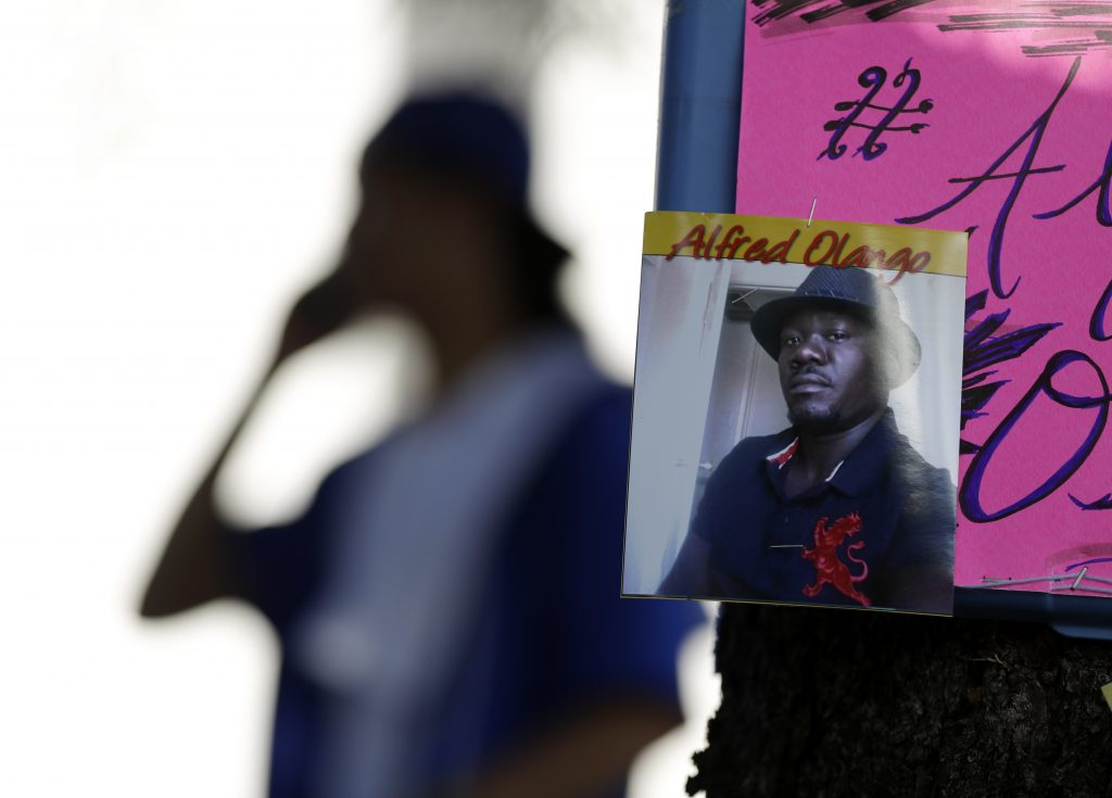 A man stands behind a picture of Alfred Olango during a protest Wednesday, Sept. 28, 2016, in El Cajon, Calif. (AP Photo/Gregory Bull)
