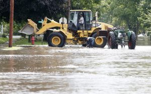 Men move a tractor to higher ground in Greene, Iowa, as the Shell Rock River rises into residential areas on Thursday. (Brandon Pollock/The Courier via AP)