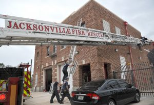 Jacksonville firefighters install storm shutters at Jacksonville Fire and Rescue's Ladder Company Four on Thursday. (Bruce Lipsky/The Florida Times-Union via AP)