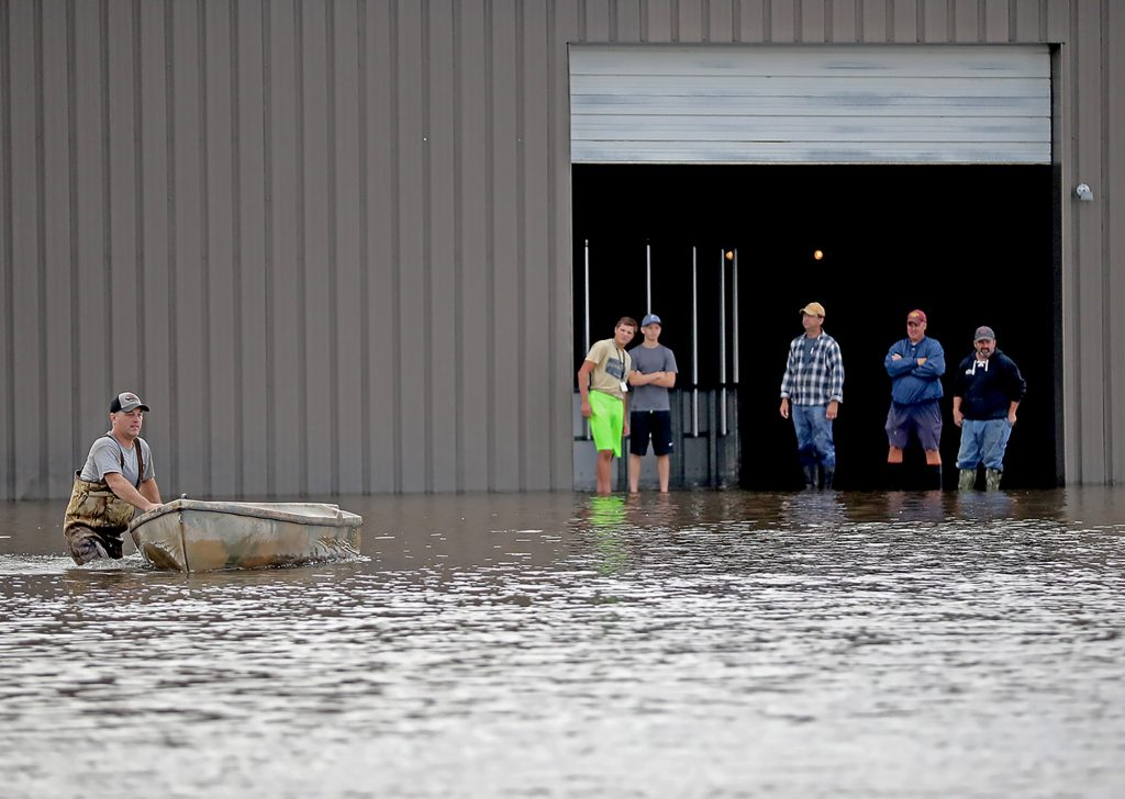 Men prepare to help sand an ice arena in Waseca, Minn., on Thursday. Several Midwestern states were experiencing floods Thursday after up to 10 inches of rain fell in parts of Minnesota, Wisconsin and Iowa.  (Elizabeth Flores/Star Tribune via AP)