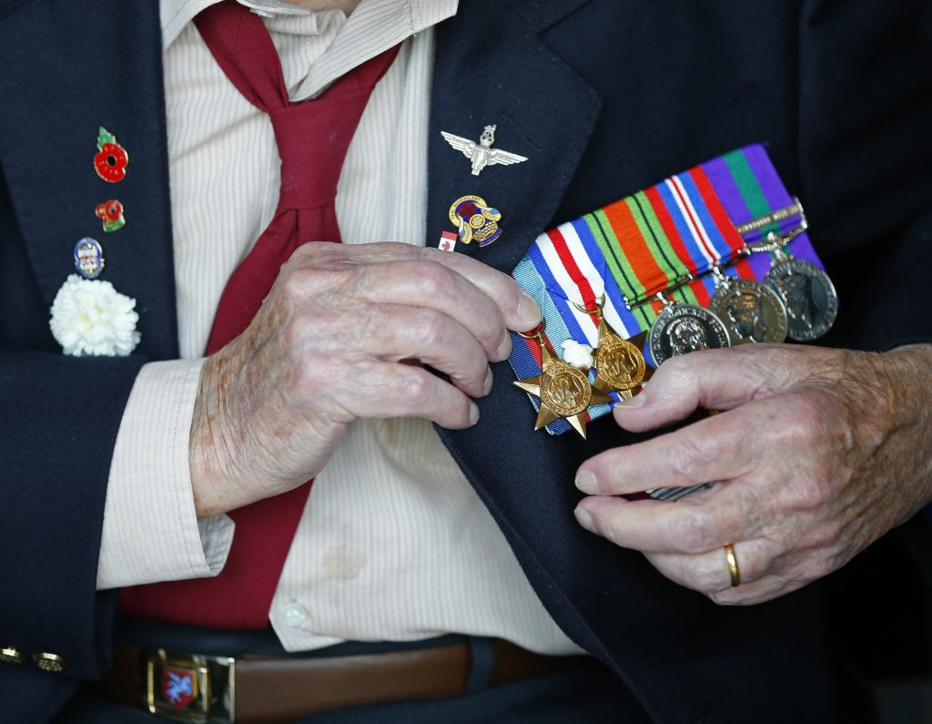 A World War II veteran adjusts his medals prior to the arrival ceremony for an American flag carried during D-Day in 1944 at the National Military Museum in Soesterberg, Netherlands, Thursday, Sept. 15. (AP Photo/Peter Dejong)