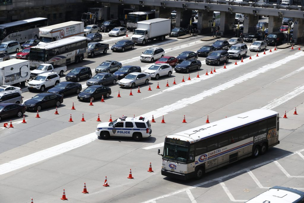 FILE - A bus waits to be diverted into a congested tube on the New Jersey side of the Lincoln Tunnel in Weehawken, N.J. (AP Photo/Julio Cortez)