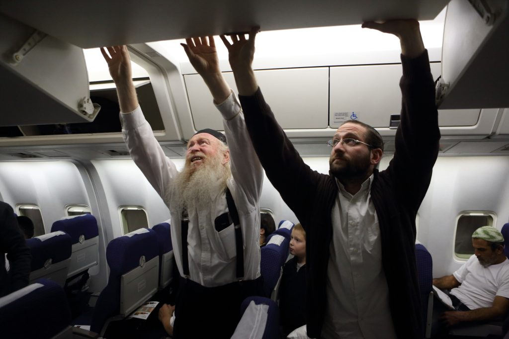 Passengers tuck their suitcases into overhead compartments before taking off to Uman, Ukraine, for Rosh Hashanah in 2013. (Yaakov Naumi/Flash90)