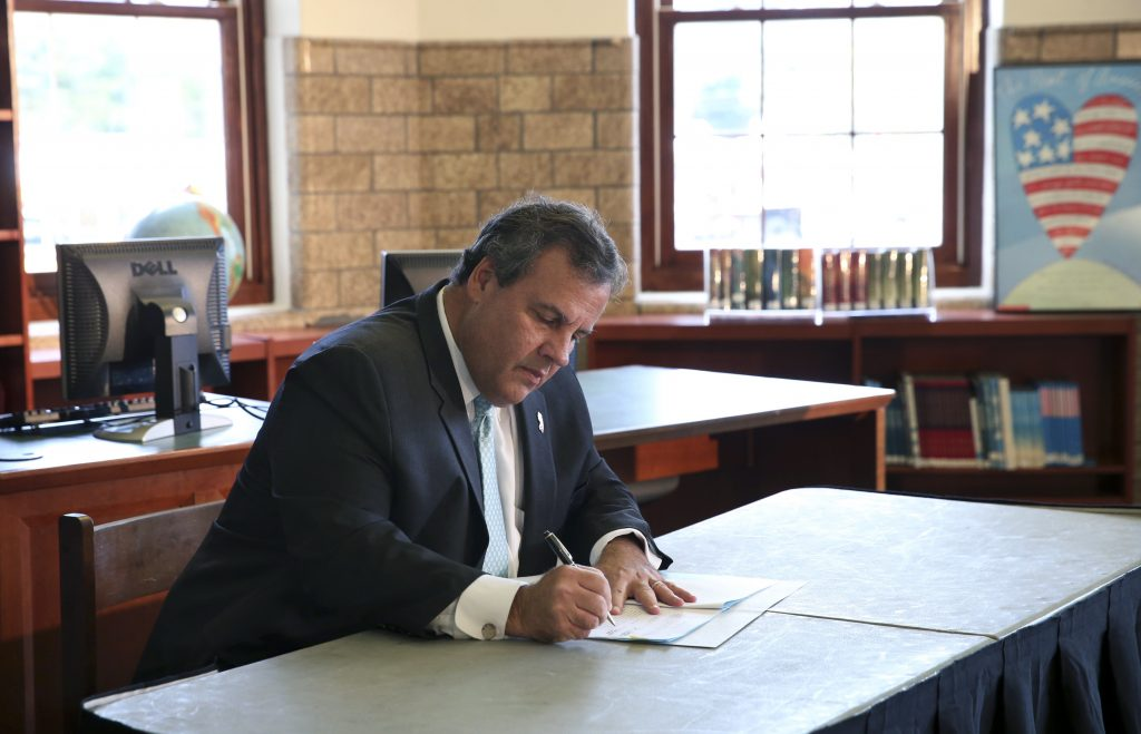 New Jersey Gov. Chris Christie on Tuesday signs an education bill in the Grover Cleveland Middle school library in Caldwell, N.J. (AP Photo/Mel Evans)