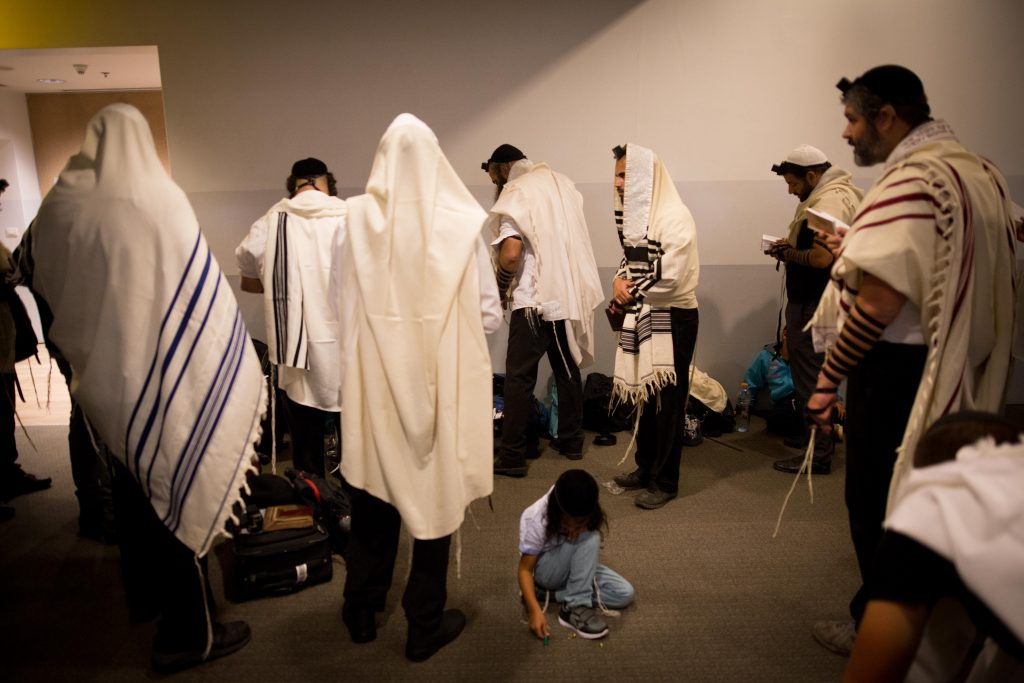 Ultra orthodox Jewish men pray as they make there way to Uman for the Jewish holiday of Rosh Hashanah at the Ben Gurion international airport near Tel Aviv early on September 29, 2016, worshipers are expected to visit the grave of Rabbi Nachman of Breslov in Uman during the holiday of Rosh Hashanah. Photo by Yonatan Sindel/Flash90 *** Local Caption *** ÷áø ø' ðçîï îáøñìá îæååãåú çøãé àåîï áøñìá îèåñ éìãéí ùãä úòåôä ðñéòä