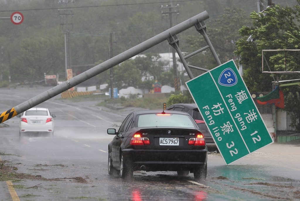 A car drives past a collapsed traffic sign in Kaohsiung, Taiwan. (Reuters/Stringer)