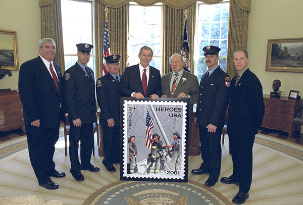 "White House photo of March 11, 2002, unveiling of ""Heroes"" stamp. From left: Postmaster General Jack Potter; New York City Fire Department Firefighters Billy Eisengrein and George Johnson; President George W. Bush, U.S. Rep. Gary Ackerman, 5th District, N.Y.; Firefighter Dan McWilliams; and Record photographer Thomas Franklin, who took the photo featured on the stamp. (White House Photo)"