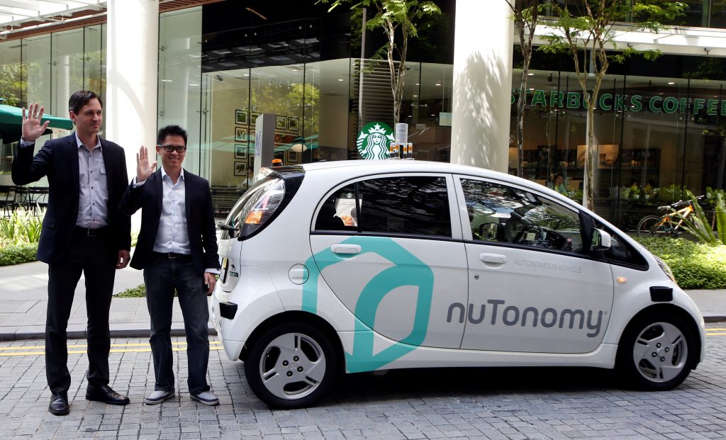 CEO of nuTonomy Karl Iagnemma (L) and Grab's Head of Singapore Lim Kell Jay pose next to a driverless car in Singapore September 23, 2016. REUTERS/Edgar Su