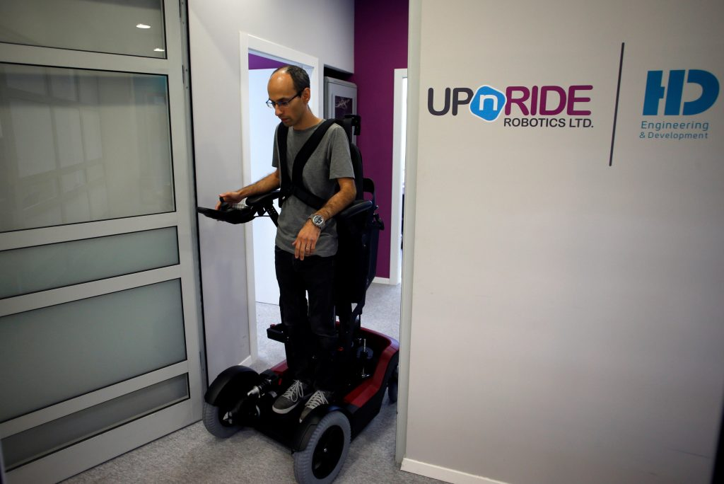 An employee stands on a wheelchair developed by Israeli company UPnRIDE Robotics, that enables paralysed people with limited function in their arms to stand upright, during a demonstration at their offices in Yoqneam, Israel September 6, 2016. REUTERS/Baz Ratner TPX IMAGES OF THE DAY