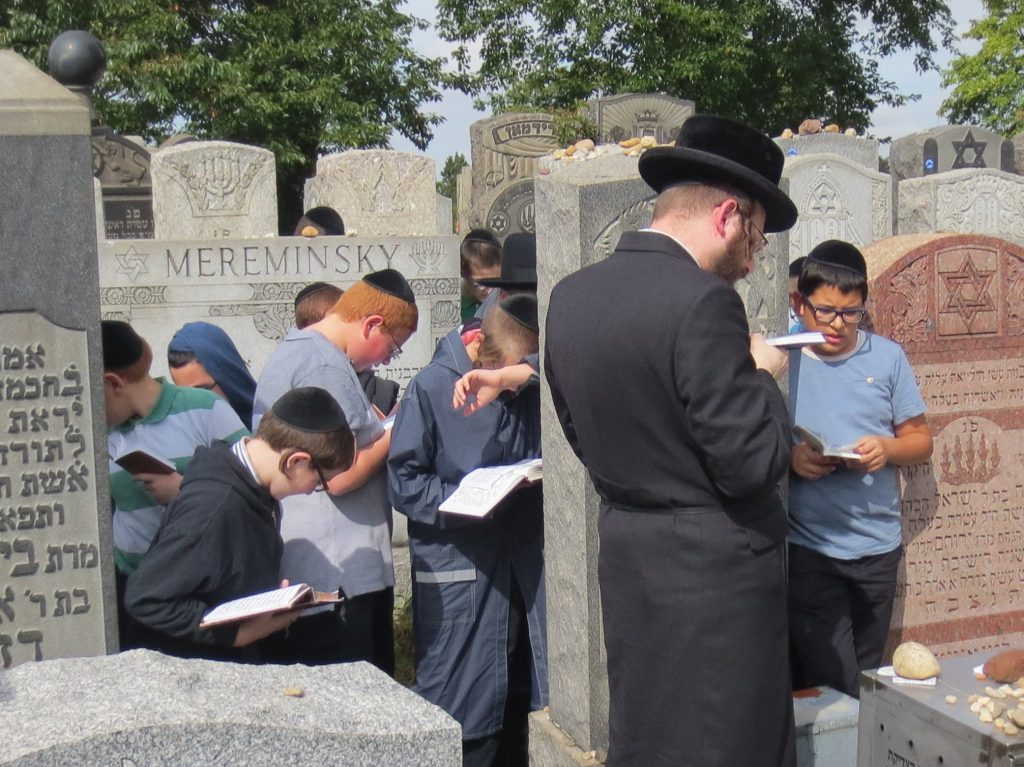 7th Grade Talmidim of Yeshiva Ch'san Sofer being mispalel at the kever of the Chofetz Chaim's Rebbetzin, son and daughter, on the day of the Chofetz Chaim's Yartzeit.