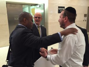 Prosecutor Howard Jackson (left) and Yitzy Stark embrace in the lobby of the courthouse after the verdict. In the center is Chris Blank of the Brooklyn district Attorney's office, whom Jackson credited with spending numerous hours gathering the evidence, particularly related to cellphone records, that the prosecution used to build its case. (Yosef Caldwell/Hamodia)