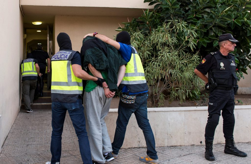 Spanish police officers lead a detained man into a police station during an operation in Melilla, southern Spain, September 28, 2016. REUTERS/Jesus Blasco De Avellaneda
