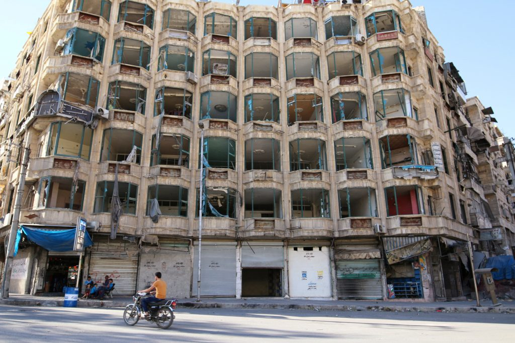A man rides a motorcycle past a damaged building in the rebel-held al-Shaar neighbourhood of Aleppo, Syria, September 17, 2016. Picture taken September 17, 2016. REUTERS/Abdalrhman Ismail