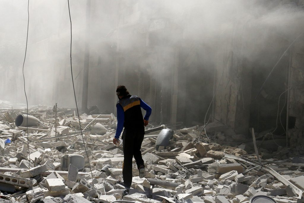 A man walks on the rubble of damaged buildings after an airstrike on the rebel held al-Qaterji neighbourhood of Aleppo, Syria September 25, 2016. REUTERS/Abdalrhman Ismail