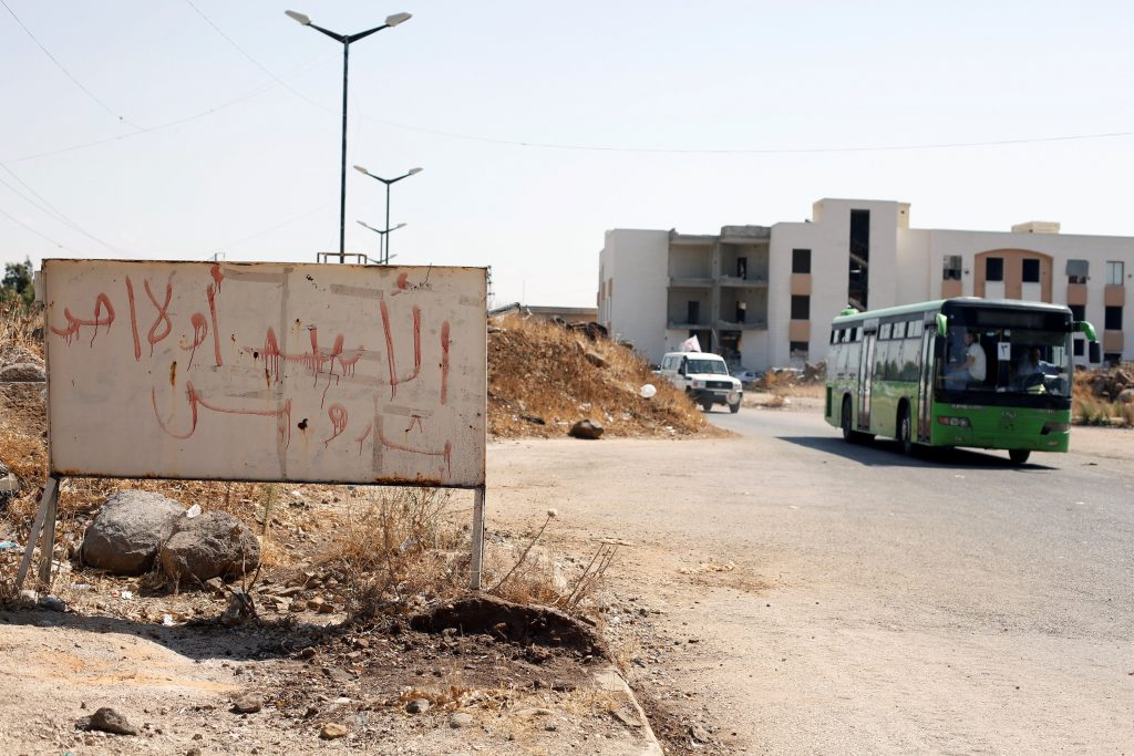 """A bus with Syrian rebels and their families evacuating the besieged Waer district in the central Syrian city of Homs is pictured after a local agreement reached between rebels and Syria's army, Syria, September 22, 2016. The graffiti on the sign reads in Arabic:"""" Assad or nobody, only Bashar."""" REUTERS/Omar Sanadiki TPX IMAGES OF THE DAY"""