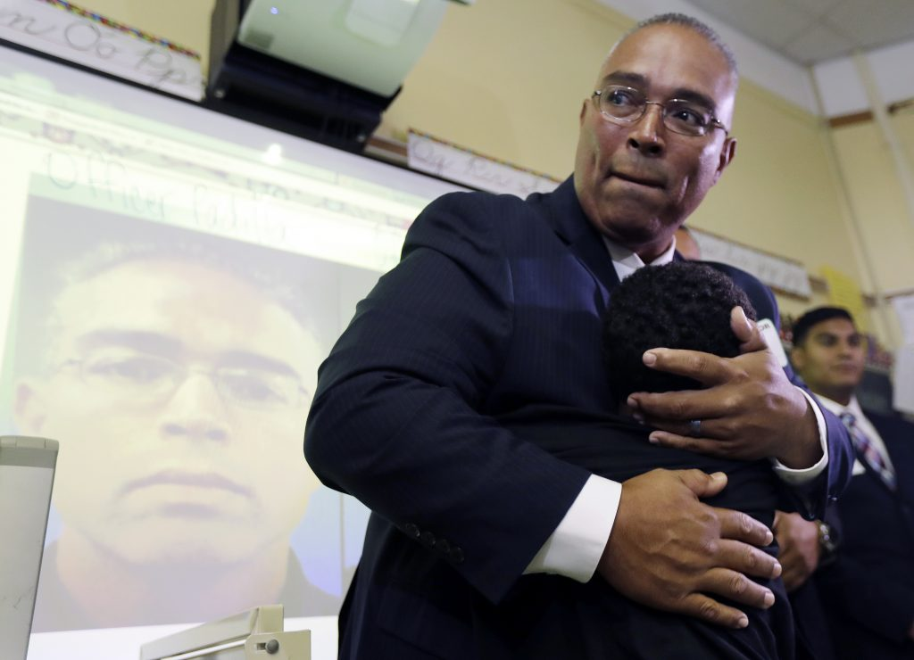 Linden Police officer Angel Padilla on Thursday hugs Jeremiah Butler Knight, a third-grade student at Linden School No. 5, during a visit to the school. (AP Photo/Julio Cortez)