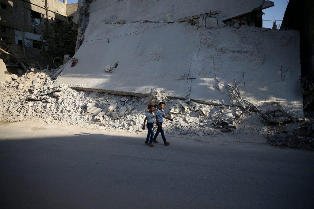 Boys walk near a damaged building on the first day of Eid al-Adha celebrations in the rebel held Douma neighbourhood of Damascus, Syria September 12, 2016. REUTERS/Bassam Khabieh