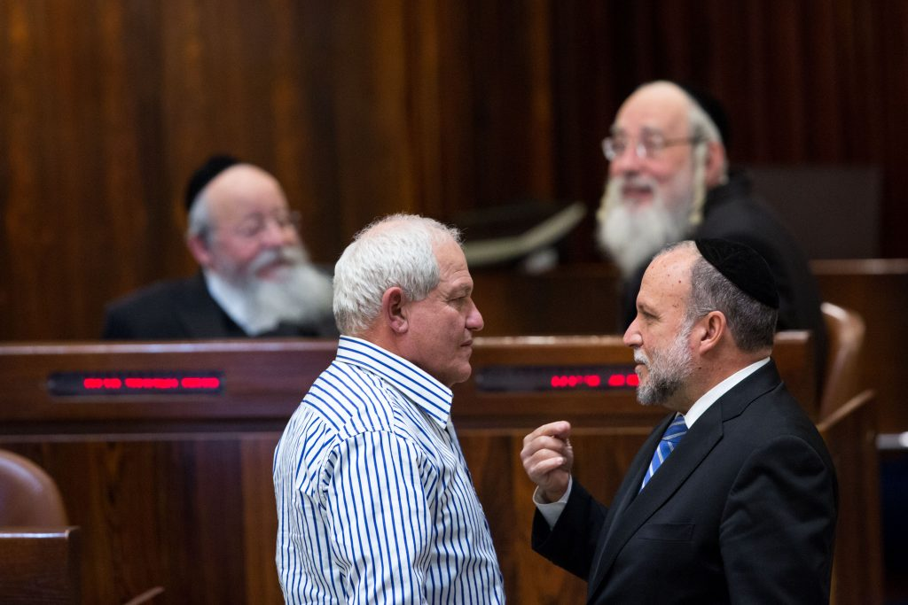 Minister of Welfare and Social Services Haim Katz (Likud) (L), talking with Shas MK Yitzhak Cohen (R) in the Knesset. (Miriam Alster/Flash90)