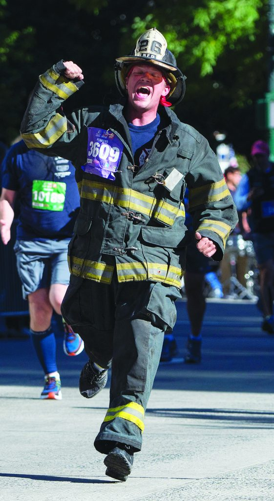 """A firefighter near the finish line Sunday during the """"Stephen Siller Tunnel to Towers"""" run in New York. (AP Photo/Craig Ruttle)"""