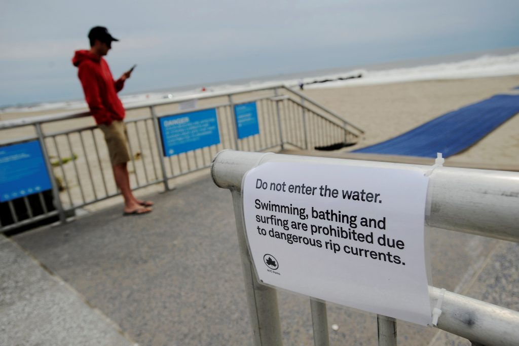 A sign warns of water closures at Rockaway Beach in Queens, New York on Labor Day due to post-tropical cyclone Hermine which tracked off the east coast of the U.S. September 5, 2016. REUTERS/Mark Kauzlarich