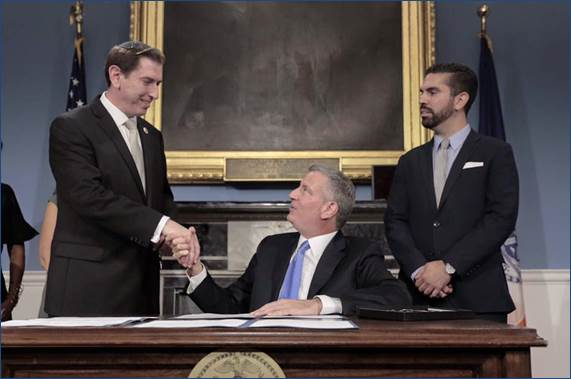 Mayor Bill de Blasio shakes Councilman Chaim Deutsch's hand Wednesday at a City Hall ceremony after he signed the Senior Scam Education Bill into law. (Office of Councilman Deutsch)