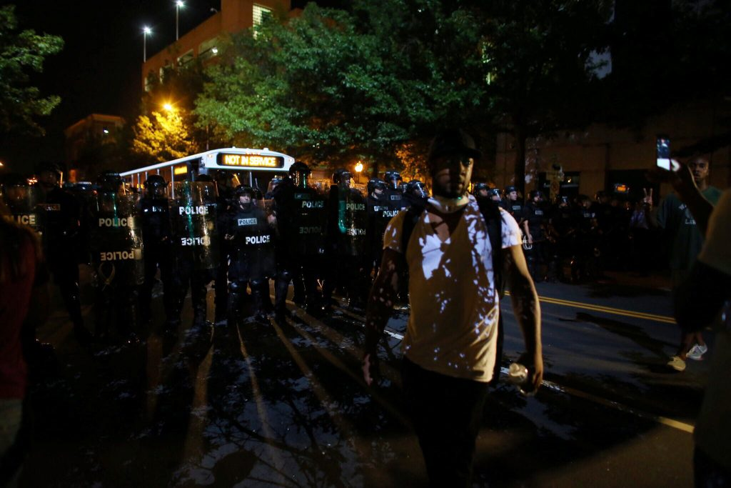 Demonstrators confront police in riot gear after a midnight curfew while protesting the police shooting of Keith Scott in Charlotte, North Carolina, U.S., September 25, 2016. REUTERS/Mike Blake