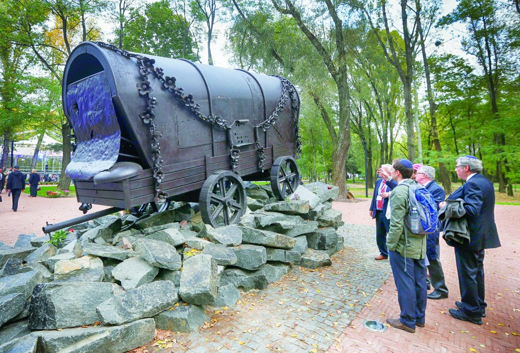 Visitors look at a monument at Babi Yar ravine, where Nazi troops machine-gunned tens of thousands of Jews and others during World War II, in Kiev, Ukraine, Thursday, Sept. 29. Ukraine was marking the 75th anniversary of the 1941 Babi Yar massacre. (AP Photo/Efrem Lukatsky)