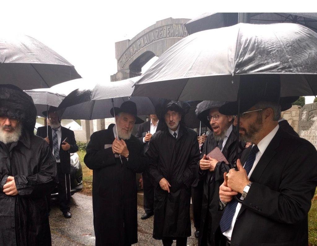 Talmidim of Rav Pam at his kever on his yahrzeit, being addressed by Rabbi Yosef Eisen. (L-R) Rabbi Dovid Scheinfeld, Rabbi Matis Blum,Yonah Blumenfrucht, Yisroel Blumenfrucht, Rabbi Yosef Eisen (speaking); Nussie Motechin