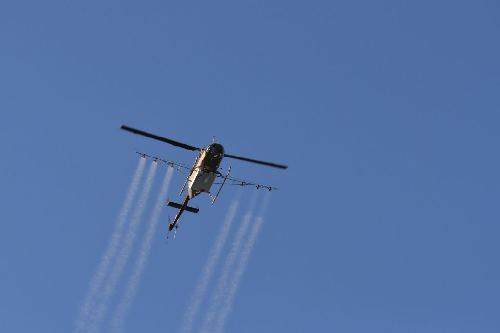 A helicopter spraying mosquito pesticide.