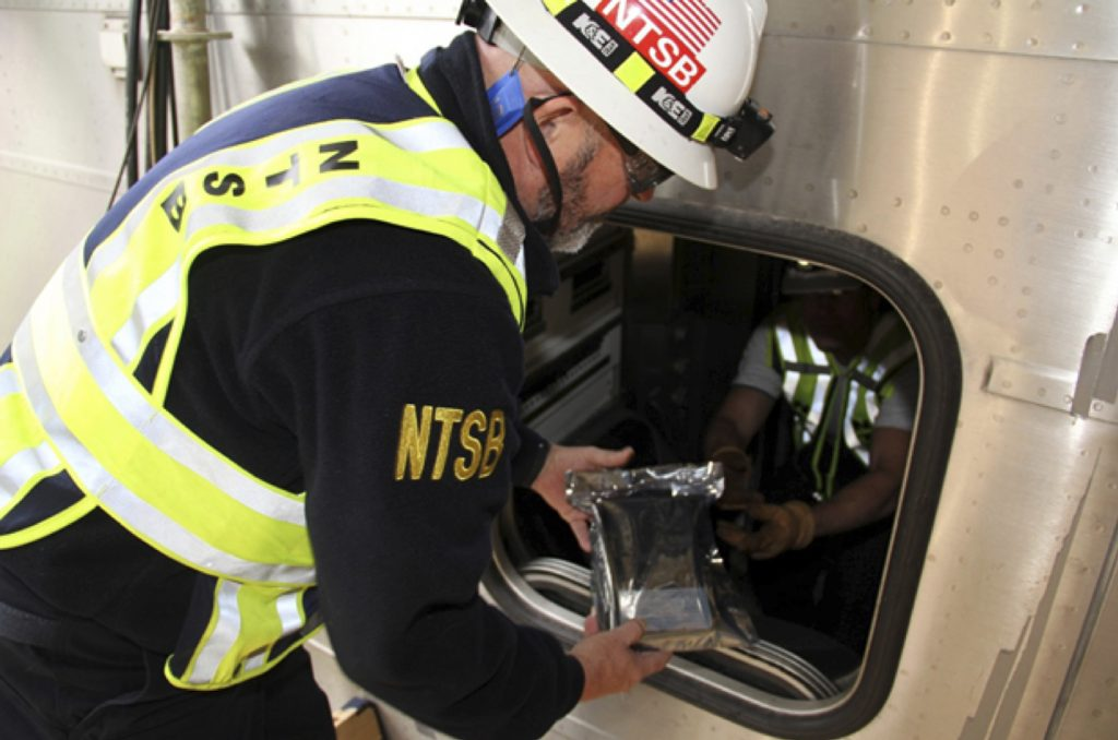 In this photo released by the National Transportation Safety Board (NTSB), James Southworth, Investigator-in-Charge for the National Transportation Safety Board's investigation, is handed the lead car's video recorder in an anti-static bag from NTSB investigator Michael Hiller, Tuesday, Oct. 4, 2016, in Hobokon, N.J. Federal investigators recovered a data recorder, video recorder and the engineer's cellphone Tuesday from the commuter train that crashed into a New Jersey rail station last week. The items were sent to an agency lab for analysis. (N.J. Transit Police Det. Laquan Hudson/NTSB via AP)