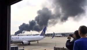 This video screencap shows smoke rising after an engine failure on an American Airlines jet (background) sparked a fire at O'Hare Airport on Friday. (Robocast.com/Handout via Reuters)
