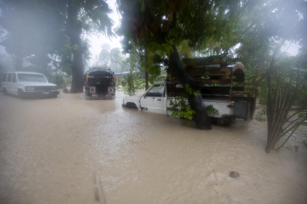 Vehicles sit stranded in flood waters in Leogane, Haiti, Tuesday, Oct. 4, 2016. Matthew slammed into Haiti's southwestern tip with howling, 145 mph winds Tuesday, tearing off roofs in the poor and largely rural area, uprooting trees and leaving rivers bloated and choked with debris. ( AP Photo/Dieu Nalio Chery)