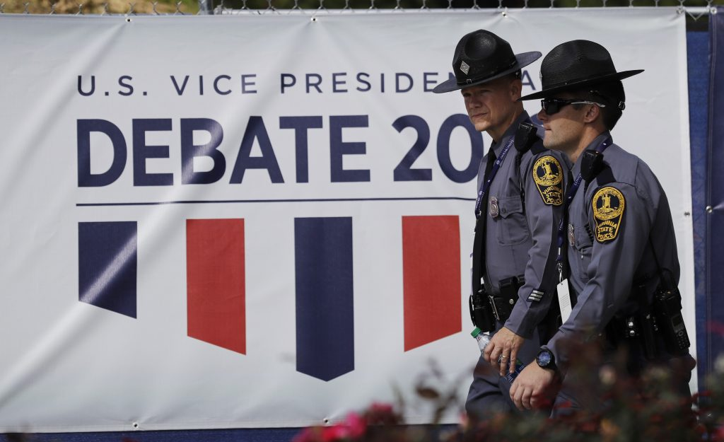 Police officers walk outside a security fence around Longwood University before the vice-presidential debate between Republican vice-presidential nominee Gov. Mike Pence and Democratic vice-presidential nominee Sen. Tim Kaine in Farmville, Va., Tuesday, Oct. 4, 2016.(AP Photo/Patrick Semansky)