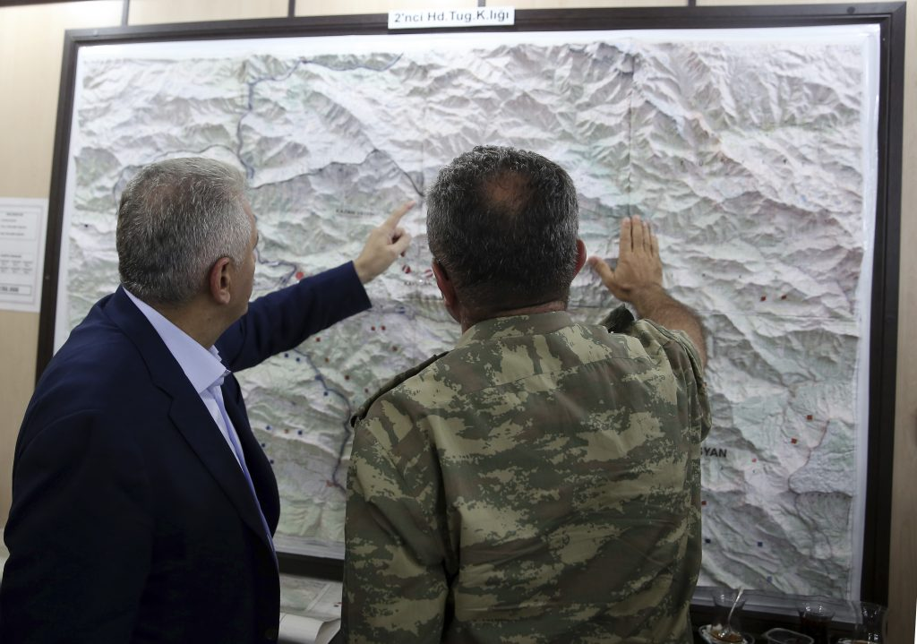 """FILE - In this Monday, Sept. 5, 2016 photo, an army commander informs Turkey's Prime Minister Binali Yildirim, left, on a Turkey-Iraq border map, in Cukurca, Turkey. Iraq's Foreign Ministry has summoned Turkeys' ambassador to Baghdad over """"provocative"""" comments by Turkish Prime Minister Binali Yildirim about the planned operation to dislodge Islamic State militants from the city of Mosul. (Prime Ministry Press Service, Pool photo via AP, File)"""