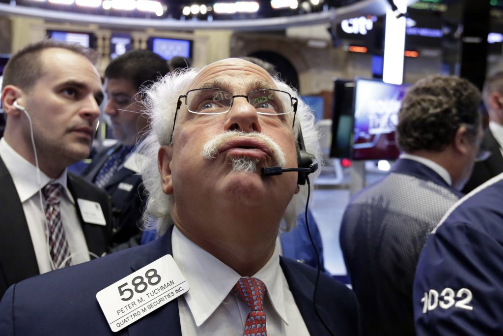 Trader Peter Tuchman, center, works on the floor of the New York Stock Exchange on Wednesday. (AP Photo/Richard Drew)