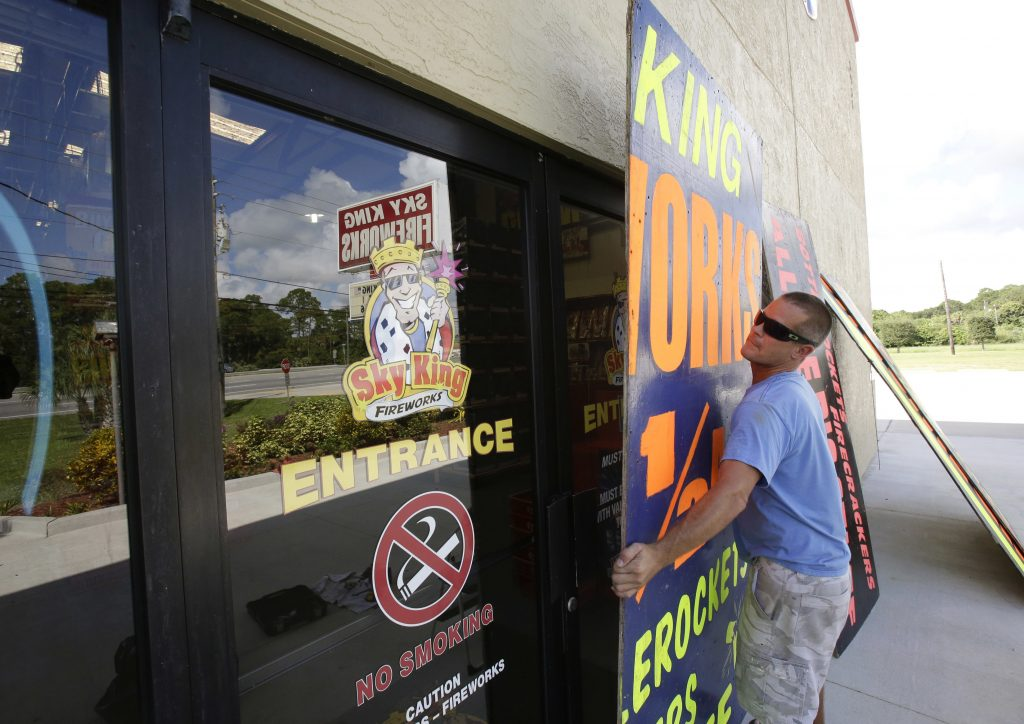 Andrew Esser boards up the glass doors at the entrance of Sky King Fireworks in Cocoa, Fla., on Wednesday, in preparation for Hurricane Matthew. (AP Photo/John Raoux)