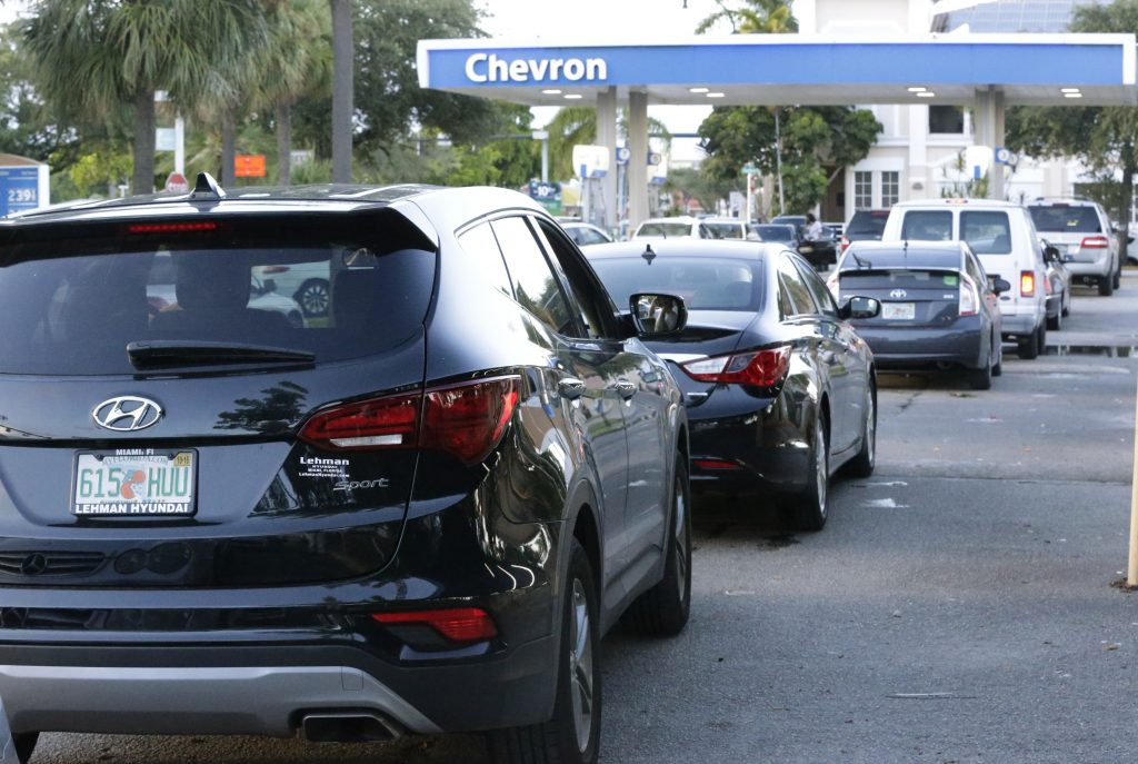 Motorists wait in a line of cars to buy gas at a Chevron gasoline station, Wednesday, Oct. 5, 2016, in Hollywood, Fla. Hurricane Matthew marched toward Florida, Georgia and the Carolinas and nearly 2 million people along the coast were urged to evacuate their homes Wednesday, a mass exodus ahead of a major storm packing power the U.S. hasn't seen in more than a decade. (AP Photo/Wilfredo Lee)
