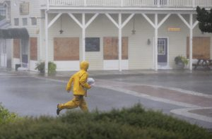 A man runs past boarded-up buildings in Saint Marys, Ga., as Hurricane Matthew begins to hit the area on Friday. (Curtis Compton/Atlanta Journal-Constitution via AP)