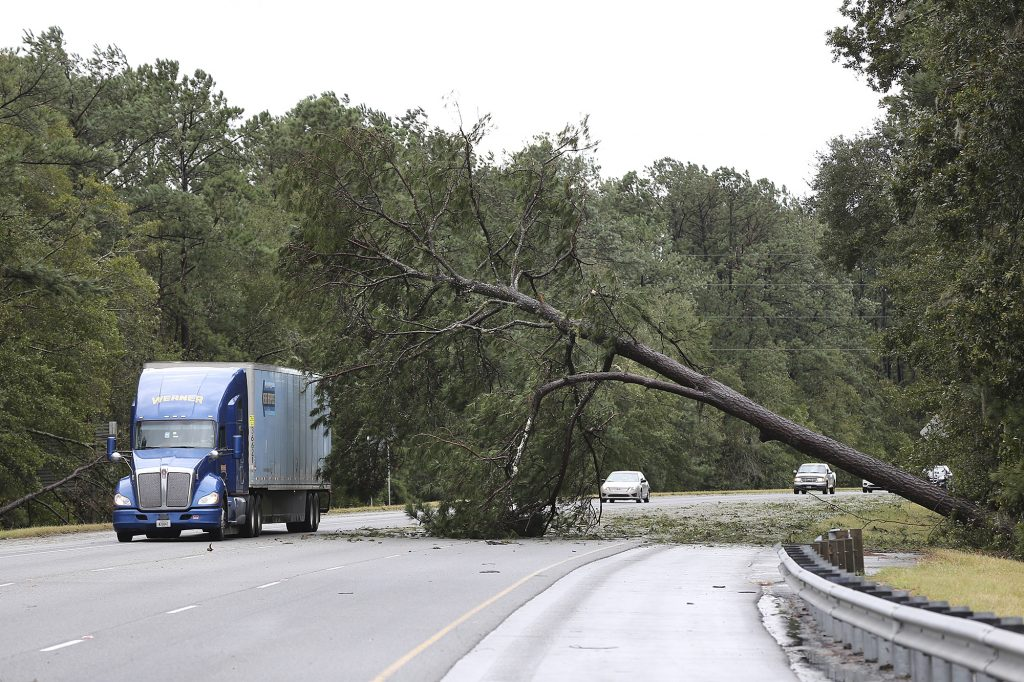 A truck passes a fallen tree caused by Hurricane Matthew on I-95 North on Saturday, Oct. 8, 2016, in Richmond Hill, Ga. Matthew is continuing its march along the Atlantic coast, lashing two of the South's most historic cities and some of its most popular resort islands with heavy rain and stiff winds. (Curtis Compton/Atlanta Journal-Constitution via AP)