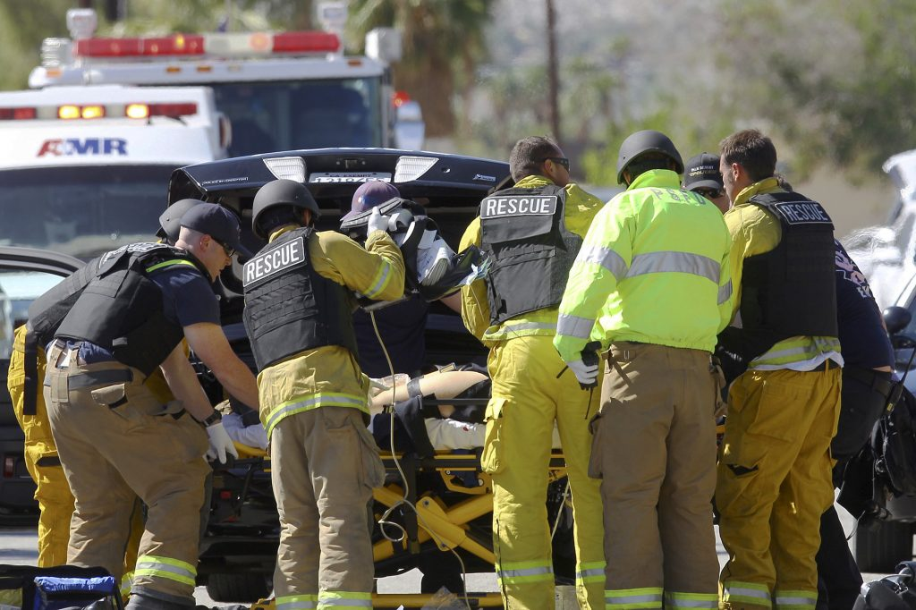 Emergency personnel wearing bullet-proof vests attend to a person on a stretcher on the corner of Cypress Road and Del Lago Road in Palm Springs, Calif. (Omar Ornelas/The Desert Sun via AP)