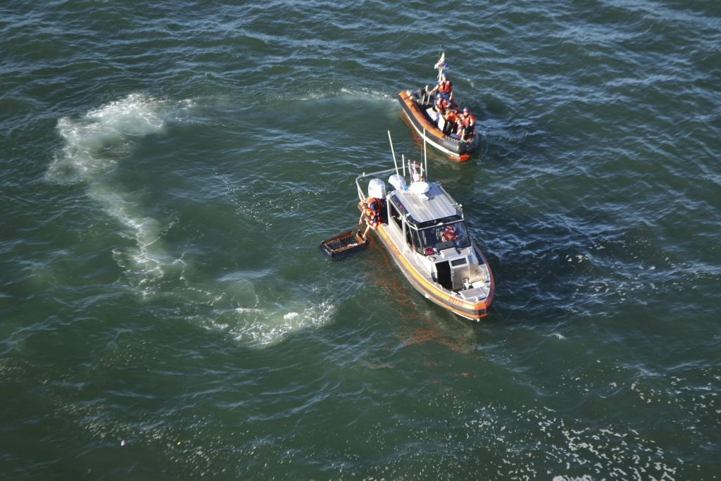 Coast Guard small boats clean up debris left behind by a boat, which capsized near Pier 45 just north of San Francisco, Calif., on Saturday. (Petty Officer 2nd Class Chris Parrinello/U.S. Coast Guard via AP)