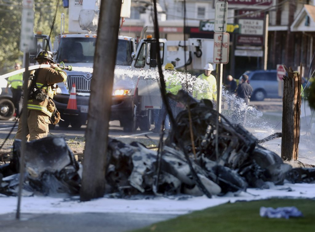 Firefighters use foam to extinguish the fire of a demolished aircraft after the plane crashed on Main Street in East Hartford Conn., Tuesday, Oct. 11, 2016. Authorities said at least one person is dead and another is injured after a small airplane crashed near the Connecticut River. (Jim Michaud/Journal Inquirer via AP)