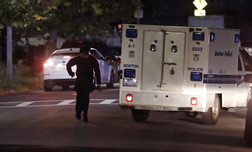 Police search for a suspect after a police shooting in the East Boston neighborhood of Boston, Wednesday, Oct. 12, 2016. Police say two officers were shot late Wednesday night. Their conditions were not immediately available. It's unclear what led to the shooting. (AP Photo/Charles Krupa)