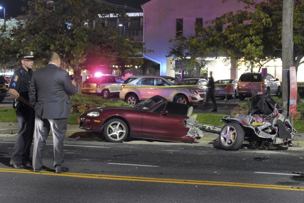 Police survey the wreckage of a Mazda Miata that was split in half after a collision with a Mercedes-Benz in Rockville Centre, Long Island, Friday. (Paul Mazza/Newsday via AP