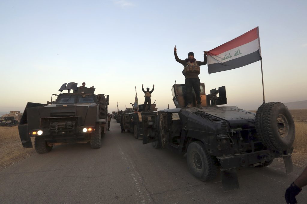 Members of Iraq's elite counterterrorism forces pose on their vehicles as they advance towards the city of Mosul, Iraq, Thursday. (AP Photo/Khalid Mohammed)