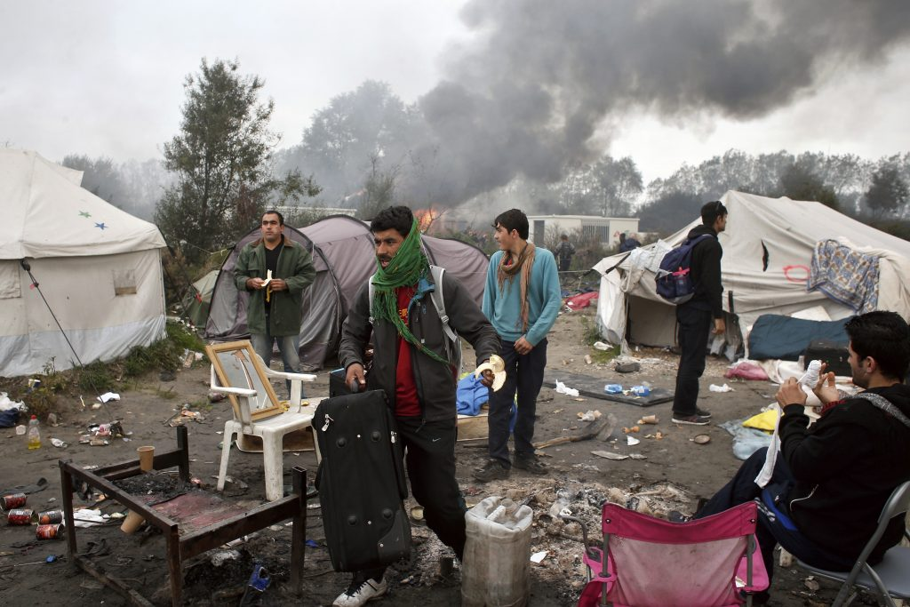 "People carry belongings as smoke and flames rise in the makeshift migrant camp known as ""the jungle"" near Calais, France, on Wednesday. (AP Photo/Thibault Camus)"